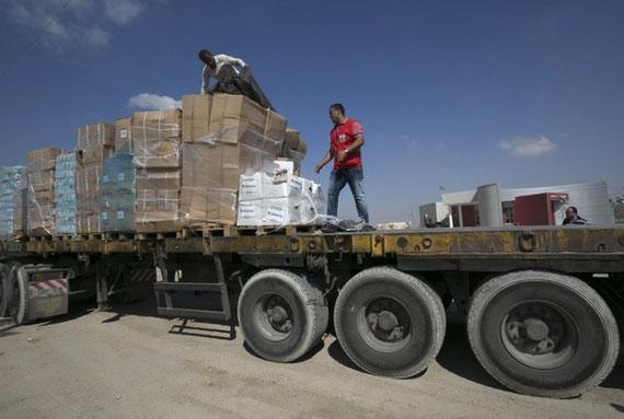 Du personnel humanitaire sur un camion chargé de colis d'aide fournis par la Turquie après son entrée dans le sud de la bande de Gaza depuis Israël en juillet 2016 (AFP)
