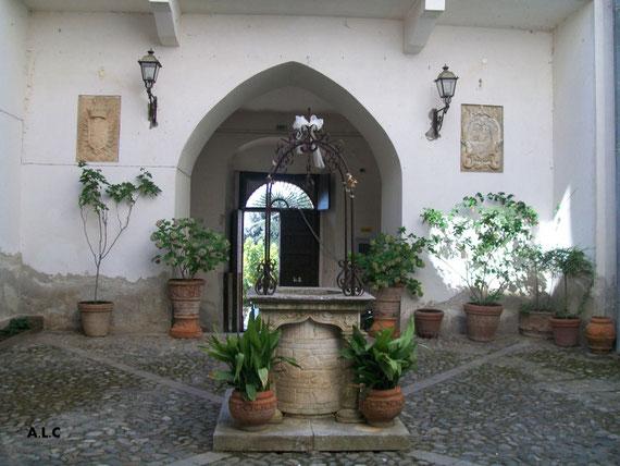 L'atrio del Castello, il pozzo e i due stemmi araldici appartenuti alle due famiglie succedutesi nella proprietà del castello