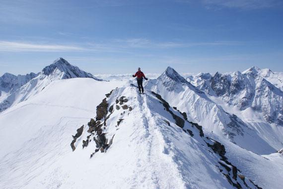 Die letzten Meter geht es zu Fuß über den Gipfelgrat zum höchsten Punkt. Im Hintergrund Roter Knopf, Glödis und Hochschober (von links nach rechts)