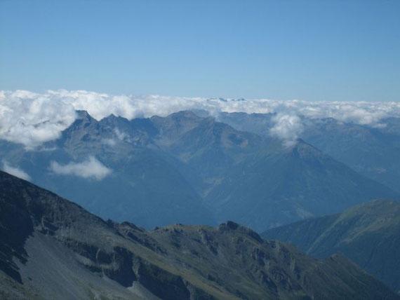 Im Süden erhebt sich die Kreuzeckgruppe und aus den Wolken ragen die höchsten Gipfel der Karnischen Alpen (Collin, Kellerspitzen und Hohe Warte) heraus