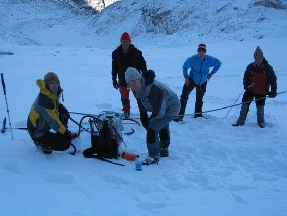 Das Team bei der Arbeit: Während zwei  Personen die Bohrung durchführen, werden vom Rest die Pegelstangen (Hintergrund) hergerichtet.
