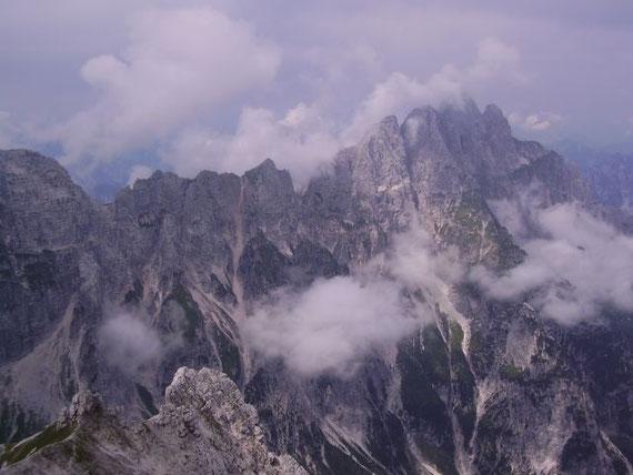 Im Westen erhebt sich der Montasch (2753m) und weiter nach links die Cima di Terrarossa (2420m) mit der Huda Paliza (Steilrinne) im Vordergrund