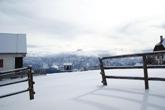 Mitten auf der Alm steht eine große Glocke, im Hintergrund die Julischen Alpen