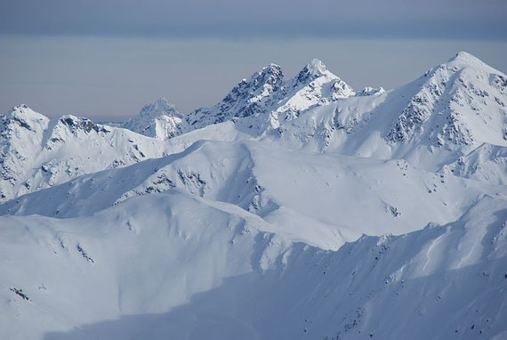 Vom Gipfel aus hat man ein herrliches Panorama, im Osten erheben sich die Karnischen Alpen mit Reiterkarspitze (weißer Doppelgipfel) und Zwölferspitz (höchster Berg in der Bildmitte)
