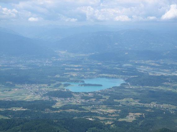 Der Blick vom Gipfel des Mittagskogels hinunter zum Faaker See, im Hintergrund die Nockberge