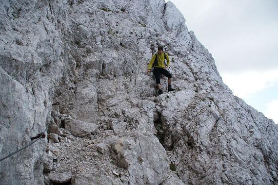 Auf steilen teils mit Seilen versichteren Bändern geht es abwärts