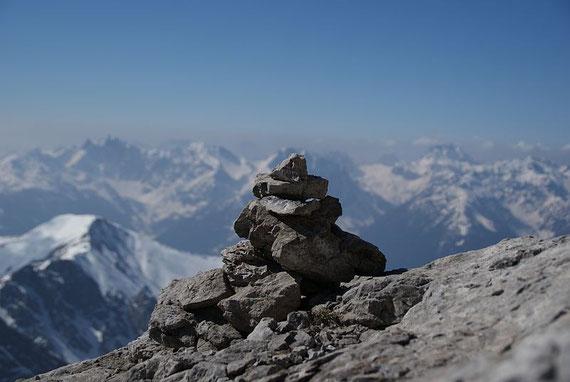 Einzelne Steinmännchen weisen den Weg; im Hintergrund die Karnischen Alpen