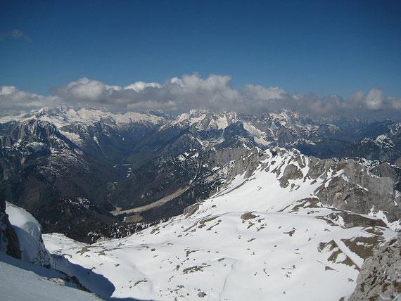 Der Blick nach Westen zum Kanin (links) und in die Wischberggruppe (Bildmitte), im Vordergrund der Kessel in dem die Mangarthütte liegt