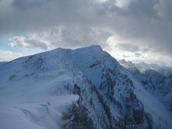 Nach Süden hin erhebt sich der Große Frauenkogel, im Hintergrund sind die Julischen Alpen zu erkennen