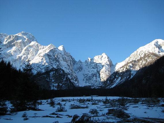 Beim Zustieg über die flache Wiese, links im Bild erhebt sich der Mangart (2677m) und in der Bildmitte die Lahnscharte