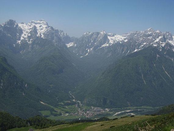 Tief im Tal liegt Mojstrana umrahmt von Triglav, Stenar und Skrlatica (von links nach rechts)