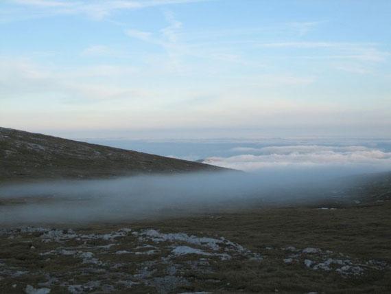 Flache Nebel knapp unterhalb des Gipfels, im Tal liegt Hochnebel