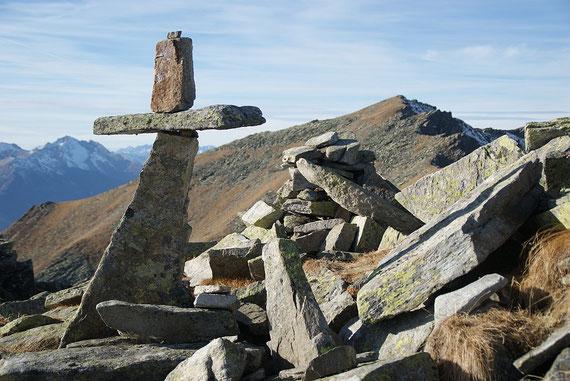 Das kleine aber feine steinerne Kreuz auf der Gurglitzen; im Hintergrund das letzte Ziel der Kammwanderung, das Hocheck