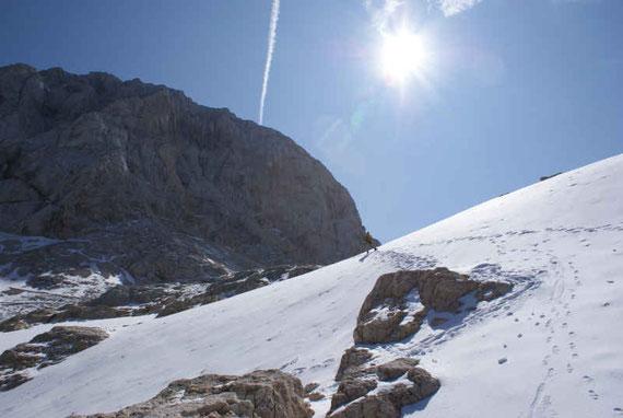Am Weg über das Hochplateau gilt es einzelne Schneefelder zu queren, links der Gipfel