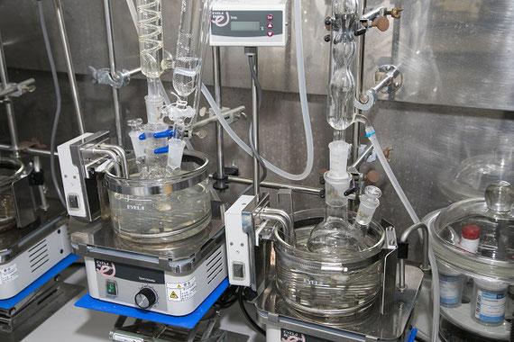 新規抽出剤(有機化合物)を合成するための実験装置。この実験では、フラスコや冷却管、滴下漏斗などの様々なガラス器具を使用します。