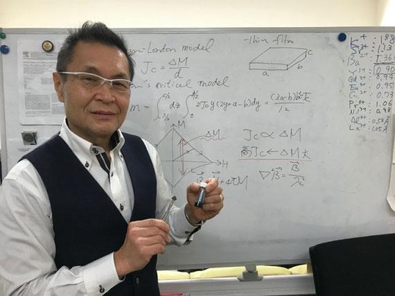 作製した高温超伝導膜 説明:左手に持っているものは超伝導薄膜を作るための原料溶液。この溶液を基板に塗布・熱処理(図2の装置)して超伝導膜を作製する。右手に持っているのは研究室で作製した超伝導薄膜。この薄膜は1平方センチメートルあたり480万アンペアもの電流を流す事ができる性能を持っている。