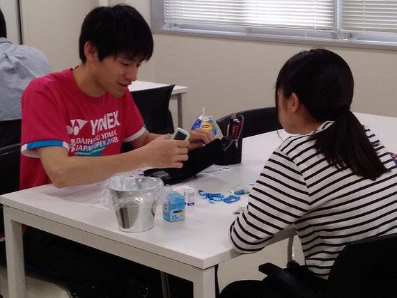 言語技術トレーニング実習の様子 。本原稿で紹介したJALパイロットも行っておられる言語技術トレーニングについて、医療系学生版のトレーニングを行っている様子です。糖尿病患者用の自己血糖測定装置による血糖値測定方法について模擬患者(学生)に対しての説明方法の訓練風景です。言語技術に沿った説明を行うことで、患者に対してわかりやすくかつ間違いなく操作方法を伝えられるかを実践的に学びます。