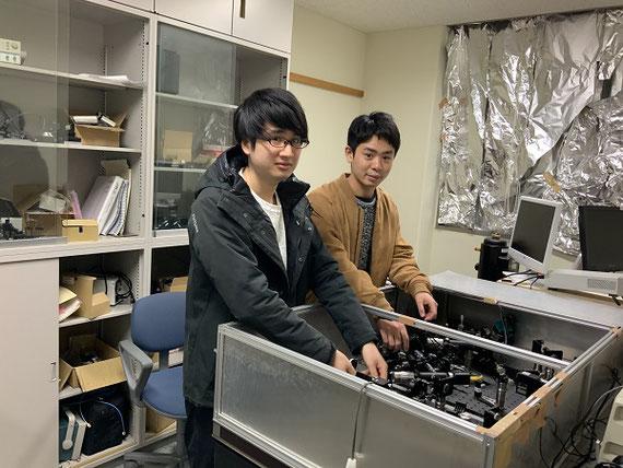 研究風景(レーザー計測)。金属ナノ粒子の性能は、レーザー光を使って試験します。レーザー光は数多くの鏡やレンズを通過した後に金属ナノ粒子に照射します。金属ナノ粒子より現れるごく微弱な光を検出するため、実際の実験は部屋全体を暗くして行います。こちらに写っている2名は大学院生で、新しい光学系の設計について打ち合わせしているところです。