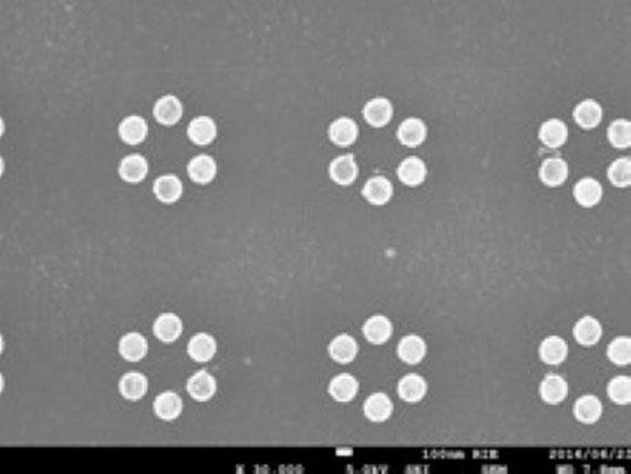 """電子顕微鏡写真。製作した金属ナノ粒子の一例です。写真中の円形に写っている物体が金のナノ粒子でその大きさは100 nm(1nmは 1/10,000,000cm)くらいです。六角形状に並んでいて、ベンゼンのように見えないでしょうか。実際個々の金ナノ粒子を""""原子""""、6個並べると""""分子""""と見立てると、原子と分子を繋ぐ共有結合に類似した効果が見られます。"""