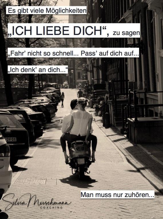 Ein Paar fährt auf einem Roller durch eine Straße. Bild mit Text.