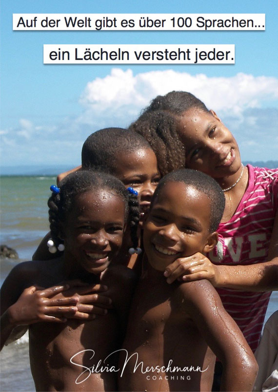 Vier dunkelhäutige lachende Kinder am Strand. Bild mit Text.