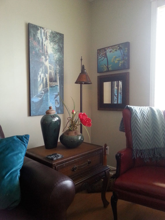 Sometimes corners are dark and empty but this one has a lamp to read by and an interesting grouping of art and an mirror. The pair of smaller pieces is centered on the taller picture.