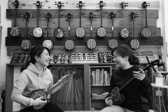 向かい合って三線を楽しそうに弾いている2人の女の子