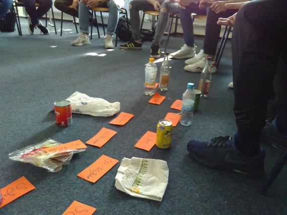 Zeitstrahl mit Zersetzungszeiten verschiedener Materialien, Plastik- und Glasflaschen, Papiertüte, Stuhlkreis, Zettel mit Angaben von Zersetzungszeiten