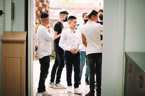 נער העולה לתורה עם חבריו בכניסה לבית הכנסת