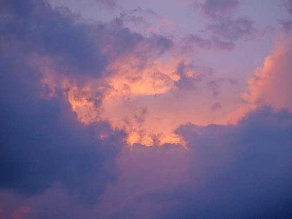 rosa Abendwolken hinter dunklen blauen Wolken