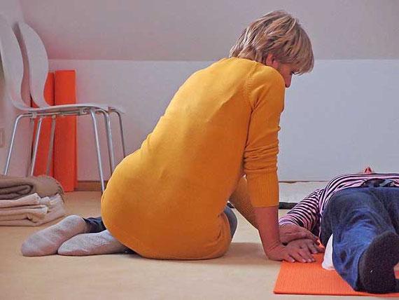 Frau berührt eine andere Frau an der Hand im Gruppen-Coaching