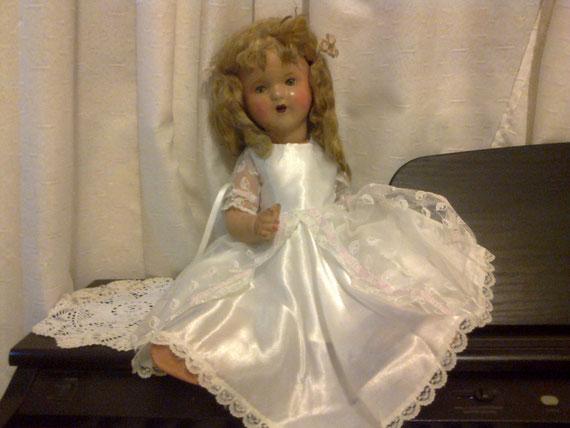 Muñeca con carita de porcelana y cuerpo de cartón piedra.