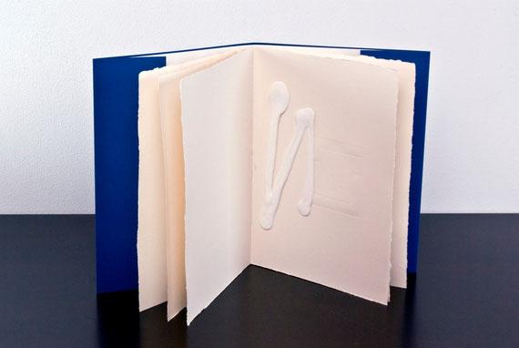 il libro aperto con l'opera bianca su pagina stampata a secco