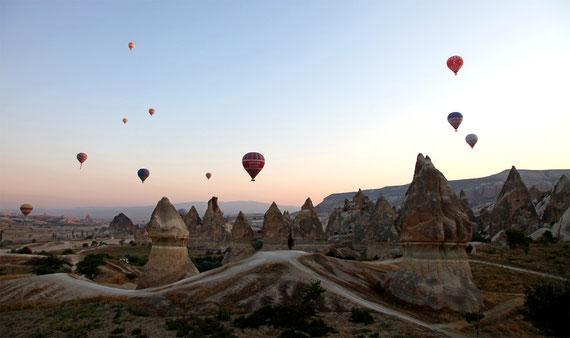 Bei Sonnenaufgang im Heissluftballon über die Tuffsteinlandschaft Kappadokiens schweben.