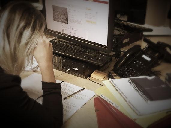 La photo décrit une femme débordée à son travail, la fatigue et le stress sont visibles.