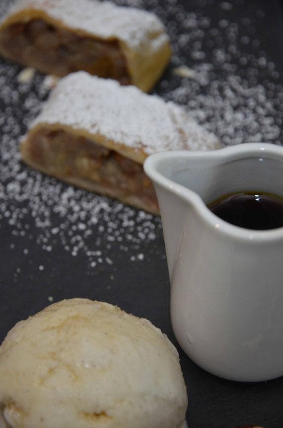 Serviervorschlag: Birnenstrudel mit Puderzucker überzogen, Vanilleeis und Kaffee-Chai-Sirup.