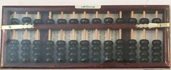 """Ábaco japonés """"soroban"""" posterior a la II Guerra Mundial, 13 columnas, año 2001, en su envoltorio, 24x9 cm"""