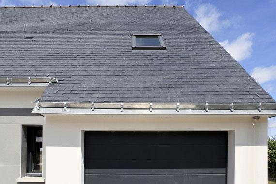 Aperçu d'une toiture d'une maison à étage en charpente traditionnelle avec ardoises naturelles et un enduit blanc et gris