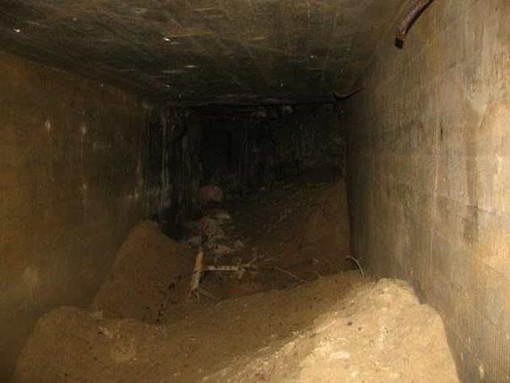 Коридор подземного каземата. Внутри можно видеть массивные наносы песка