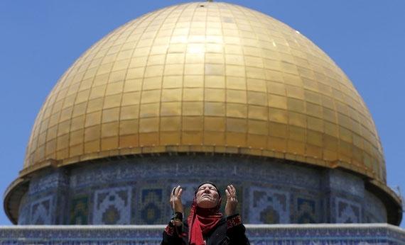 Une Palestinienne prie devant le Dôme du Rocher à Jérusalem (Reuters)