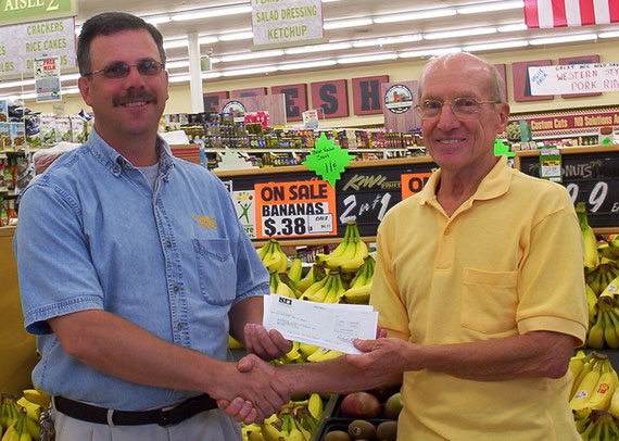 Bob Douglas, left, Macomb County Market store director, presents a matching grant check from County Market and Pepsi, to Gil Belles, of the McDonough County Historical Society for its cemetery sign project.