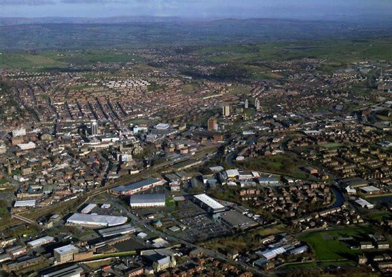 Ariel view of Blackburn town centre and beyond; Pendle Hill nestled amongst the Pennine foothills to the North West