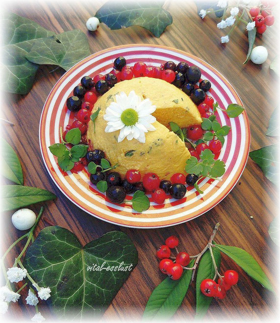 veganer Gouda-Käse mit Heidelbeeren und Johannisbeeren auf einem roten Teller