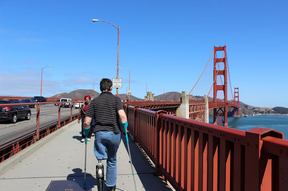 Mann mit Prothese und Krücken läuft auf der Golden Gate Bridge