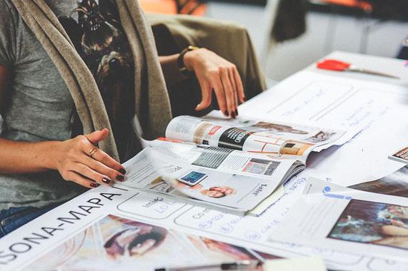 Frau sitzt am Tisch und liest in einer Zeitschrift
