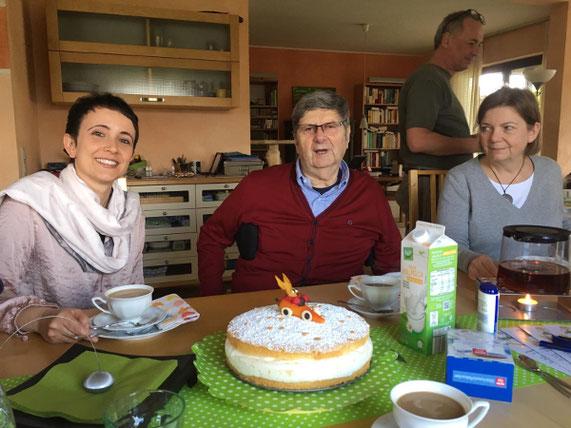Zwei Frauen und ein Mann sitzen am Kaffeetisch. Ein Kuchen mit einem Hasen aus Marzipan steht darauf.
