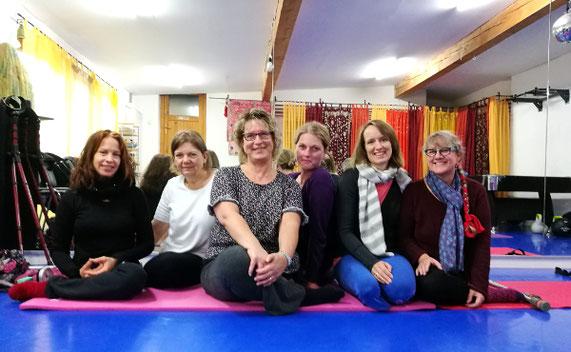 6 beinamputierte Frauen sitzen in einem Tanzraum auf einer Yogamatte.