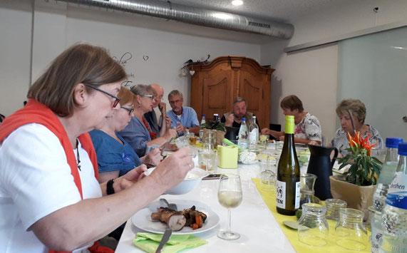 Menschen sitzen zum Essen an einem Tisch