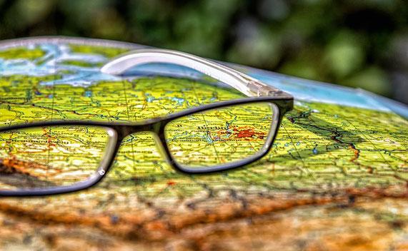 Eine Brille die auf einem aufgeschlagenen Atlas liegt