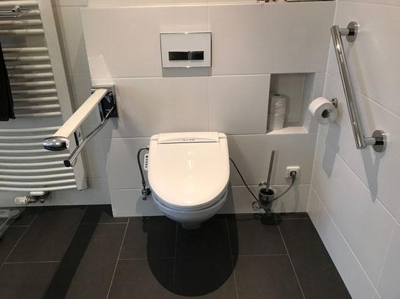 Barrierefreies Bad. Toilette mit Haltegriffen.